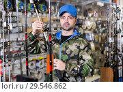 Fisherman customer in fishing clothing choosing fishing rod. Стоковое фото, фотограф Яков Филимонов / Фотобанк Лори