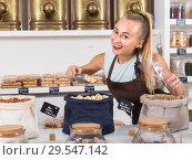 Купить «Young woman is offering nuts», фото № 29547142, снято 4 сентября 2017 г. (c) Яков Филимонов / Фотобанк Лори