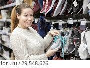 Купить «Женщина выбирает кроссовки в магазине», фото № 29548626, снято 9 декабря 2018 г. (c) Кекяляйнен Андрей / Фотобанк Лори