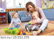 Купить «Mentor and 1 years old babies playing with educational toys in kindergarten», фото № 29553370, снято 15 декабря 2018 г. (c) Оксана Кузьмина / Фотобанк Лори