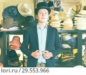 cheerful adult male shopping in botique and try on cylinder hat. Стоковое фото, фотограф Яков Филимонов / Фотобанк Лори