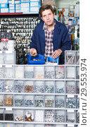 Купить «Man standing near the counter and selling details for plumbing in hardware shop», фото № 29553974, снято 4 мая 2017 г. (c) Яков Филимонов / Фотобанк Лори