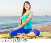 Купить «Young woman in blue T-shirt is sitting and practicing asana», фото № 29554054, снято 4 августа 2017 г. (c) Яков Филимонов / Фотобанк Лори