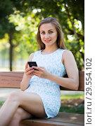 Купить «girl sitting on a bench and using phone in park», фото № 29554102, снято 8 июня 2017 г. (c) Яков Филимонов / Фотобанк Лори