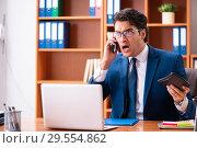 Купить «Young handsome businessman working in the office», фото № 29554862, снято 8 августа 2018 г. (c) Elnur / Фотобанк Лори