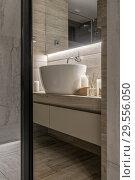 Купить «Luminous modern bathroom with textured tiled walls», фото № 29556050, снято 7 сентября 2018 г. (c) Andriy Bezuglov / Фотобанк Лори