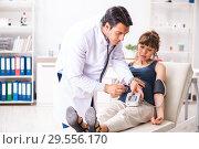Купить «Young doctor checking pregnant woman's blood pressure», фото № 29556170, снято 30 июля 2018 г. (c) Elnur / Фотобанк Лори
