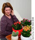 Купить «woman with a headache near the pot plants», фото № 29560938, снято 20 ноября 2017 г. (c) Володина Ольга / Фотобанк Лори