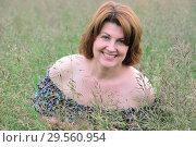 Купить «Portrait of woman in the grass on a summer day», фото № 29560954, снято 19 июня 2017 г. (c) Володина Ольга / Фотобанк Лори