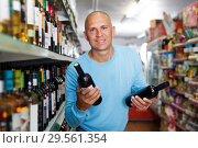 Купить «Positive man looking bottle of wine in supermarket indoors», фото № 29561354, снято 4 июля 2018 г. (c) Яков Филимонов / Фотобанк Лори