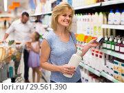 Купить «woman picking bottle with shampoo from shelf in cosmetics section in shop», фото № 29561390, снято 20 января 2019 г. (c) Яков Филимонов / Фотобанк Лори