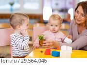 Купить «Preschool teacher with children playing with colorful toys at kindergarten», фото № 29564046, снято 26 мая 2020 г. (c) Оксана Кузьмина / Фотобанк Лори