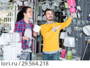 Купить «Man 29-35 and girl 17-22 years old in shop of home appliances are choosing night lamp», фото № 29564218, снято 16 февраля 2017 г. (c) Яков Филимонов / Фотобанк Лори