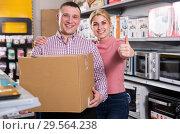 Купить «Couple with packed purchases holding thumbs up in appliances store», фото № 29564238, снято 1 марта 2018 г. (c) Яков Филимонов / Фотобанк Лори