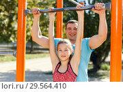 Купить «Man with daughter exercising on chinning bar», фото № 29564410, снято 29 сентября 2018 г. (c) Яков Филимонов / Фотобанк Лори