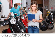 Купить «Smiling female is shopping and choosing new motobike in moto store.», фото № 29564470, снято 8 мая 2018 г. (c) Яков Филимонов / Фотобанк Лори