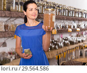Купить «adult female choosing natural dried herbs sold by weight in eco shop», фото № 29564586, снято 13 июня 2017 г. (c) Яков Филимонов / Фотобанк Лори