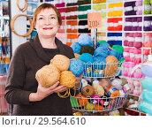 Купить «Mature woman buying yarn for their hobby on special offers», фото № 29564610, снято 10 мая 2017 г. (c) Яков Филимонов / Фотобанк Лори