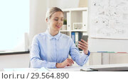 Купить «businesswoman having video call on cell at office», видеоролик № 29564890, снято 10 декабря 2018 г. (c) Syda Productions / Фотобанк Лори