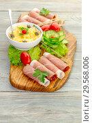 Купить «Pieces of Italian prosciutto on a wooden cutting board», фото № 29568006, снято 12 декабря 2018 г. (c) Татьяна Ляпи / Фотобанк Лори