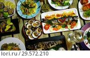 Купить «Top view of dishes from trout and mollusks served on wooden background», видеоролик № 29572210, снято 17 сентября 2018 г. (c) Яков Филимонов / Фотобанк Лори