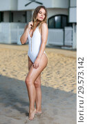 Купить «Young female in swimsuit posing near hotel at sea shore», фото № 29573142, снято 10 июля 2018 г. (c) Яков Филимонов / Фотобанк Лори