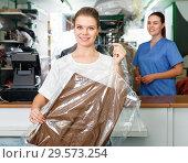 Купить «Portrait of happy young woman in modern dry cleaning with clean clothes in plastic garment bag», фото № 29573254, снято 9 мая 2018 г. (c) Яков Филимонов / Фотобанк Лори