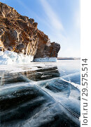 Lake Baikal in winter. Beautiful smooth ice with cracks near the rocky coast of Olkhon Island on a sunny frosty day. Стоковое фото, фотограф Виктория Катьянова / Фотобанк Лори