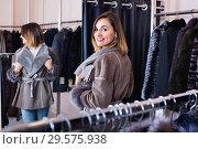 Купить «Woman trying on sheepskin coat in women's cloths store», фото № 29575938, снято 7 июля 2020 г. (c) Яков Филимонов / Фотобанк Лори