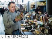 Купить «Positive senior man choosing vintage goods at flea market», фото № 29576242, снято 23 октября 2017 г. (c) Яков Филимонов / Фотобанк Лори