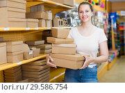 Купить «Seller shows the assortment of boxes», фото № 29586754, снято 19 апреля 2017 г. (c) Яков Филимонов / Фотобанк Лори