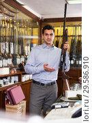 Купить «Male owner of hunting store standing with shotgun», фото № 29586910, снято 11 декабря 2017 г. (c) Яков Филимонов / Фотобанк Лори