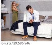 Купить «Man sitting on bed and dressing», фото № 29586946, снято 24 сентября 2018 г. (c) Яков Филимонов / Фотобанк Лори