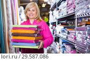 Купить «Mature female demonstrating colored bed sheet stack», фото № 29587086, снято 17 января 2018 г. (c) Яков Филимонов / Фотобанк Лори