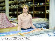 Купить «Saleswoman offering cloth in textile shop», фото № 29587162, снято 2 марта 2018 г. (c) Яков Филимонов / Фотобанк Лори