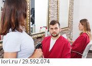 Купить «Positive man client sitting at chair in hairdressing salon», фото № 29592074, снято 25 апреля 2018 г. (c) Яков Филимонов / Фотобанк Лори