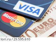 Купить «Банковские карты Visa card и MasterCard на фоне банкнот Евро», фото № 29595610, снято 23 марта 2014 г. (c) Александр Гаценко / Фотобанк Лори