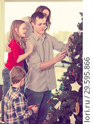 Купить «Smiling family members preparing for Christmas», фото № 29595866, снято 23 января 2019 г. (c) Яков Филимонов / Фотобанк Лори
