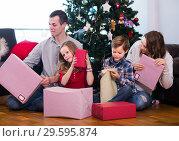 Купить «Large young family handing gifts during Christmas at home», фото № 29595874, снято 26 июня 2019 г. (c) Яков Филимонов / Фотобанк Лори