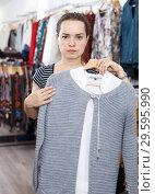 Купить «Woman holding and showing blouse on hanger», фото № 29595990, снято 10 октября 2018 г. (c) Яков Филимонов / Фотобанк Лори