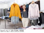 Купить «Woman holding lot of hanger with clothes», фото № 29595998, снято 10 октября 2018 г. (c) Яков Филимонов / Фотобанк Лори
