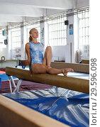 Купить «Sporty female acrobat in bodysuit practice new techniques at bars», фото № 29596098, снято 18 июля 2018 г. (c) Яков Филимонов / Фотобанк Лори