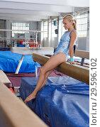 Купить «Mature sporty female gymnast in bodysuit during workout at broad bars», фото № 29596102, снято 18 июля 2018 г. (c) Яков Филимонов / Фотобанк Лори