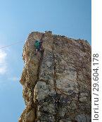 Mountaineer on a vertical fractured limestone rock against a blue sky. Стоковое фото, фотограф Сергей Журавлев / Фотобанк Лори