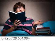 Купить «The young student preparing for exams at night at home», фото № 29604994, снято 18 сентября 2018 г. (c) Elnur / Фотобанк Лори