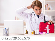 Купить «The young doctor with first aid kit in hospital», фото № 29605570, снято 23 августа 2018 г. (c) Elnur / Фотобанк Лори