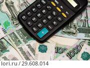 Карманный калькулятор и много российских денег. Стоковое фото, фотограф Игорь Низов / Фотобанк Лори