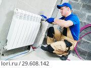 Купить «plumber at work. Installing water heating radiator», фото № 29608142, снято 16 октября 2018 г. (c) Дмитрий Калиновский / Фотобанк Лори