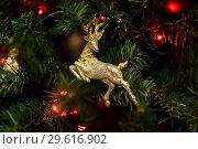 Купить «Новогодняя игрушка с изображением оленя висит на ёлке крупным планом», эксклюзивное фото № 29616902, снято 25 декабря 2018 г. (c) Игорь Низов / Фотобанк Лори