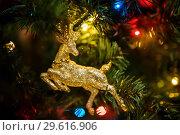 Купить «Новогодняя игрушка с изображением оленя висит на ёлке», эксклюзивное фото № 29616906, снято 25 декабря 2018 г. (c) Игорь Низов / Фотобанк Лори